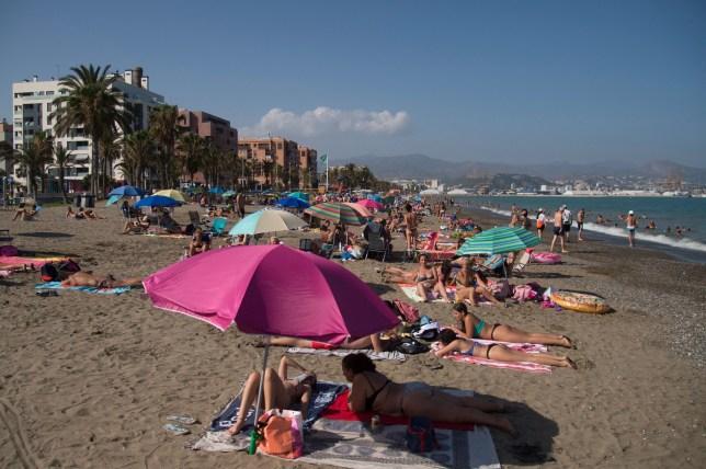 Les gens prennent le soleil sur la plage de La Misericordia à Malaga