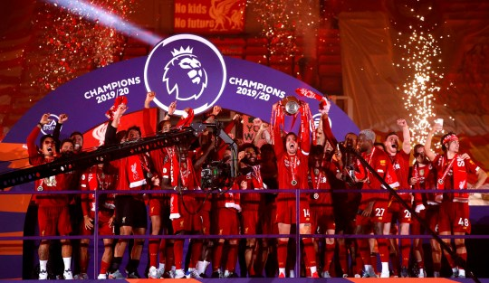 Liverpool's English midfielder Jordan Henderson (C) lifts the Premier League trophy with his team-mates during the presentation following the English Premier League football match between Liverpool and Chelsea at Anfield in Liverpool, north west England on July 22, 2020. - Liverpool on Wednesday lifted the Premier League trophy at the famous Kop stand at Anfield after their final home game of the season. With no fans able to attend due to the COVID-19 coronavirus pandemic, Liverpool said the idea for the trophy lift was to honour the club's fans, but Liverpool manager Jurgen Klopp urged fans to respect social distancing measures, after thousands gathered around the club's stadium and in the city centre following their coronation as champions last month. (Photo by PHIL NOBLE / POOL / AFP) / RESTRICTED TO EDITORIAL USE. No use with unauthorized audio, video, data, fixture lists, club/league logos or 'live' services. Online in-match use limited to 120 images. An additional 40 images may be used in extra time. No video emulation. Social media in-match use limited to 120 images. An additional 40 images may be used in extra time. No use in betting publications, games or single club/league/player publications. / (Photo by PHIL NOBLE/POOL/AFP via Getty Images)