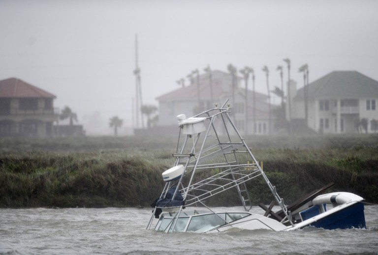 Un bateau coule dans le chenal Packery lors de l'ouragan Hanna, samedi 25 juillet 2020, à North Padre Island, Texas. La tempête de catégorie 1 a continué de se renforcer avant d'atteindre l'île Padre à 17 heures samedi. (Annie Rice / Corpus Christi Caller-Times via AP)