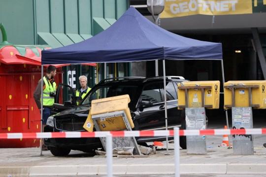 Un fonctionnaire travaille à proximité d'une voiture qui s'est écrasée sur un groupe de sept personnes à la gare Bahnhof Zoo de Berlin, Allemagne, le 26 juillet 2020.