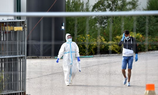 Un membre d'une équipe médicale portant des vêtements de protection se promène dans un complexe agricole à Mamming, dans le sud de l'Allemagne, le 27 juillet 2020, où une épidémie de cas de coronavirus COVID-10 chez des travailleurs saisonniers s'est produite.  - Au moins 174 travailleurs saisonniers ont été testés positifs pour le virus sur la ferme de la municipalité de Mamming, la plupart originaires de Hongrie, de Roumanie, de Bulgarie et d'Ukraine, et quelque 500 travailleurs ont été envoyés en quarantaine sur la ferme bavaroise ce week-end pour contenir une épidémie massive de coronavirus.  (Photo par Christof STACHE / AFP) (Photo par CHRISTOF STACHE / AFP via Getty Images)