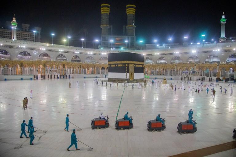 Les travailleurs nettoient pendant que les pèlerins prient devant la Kaaba à la grande mosquée pendant le pèlerinage du Haj