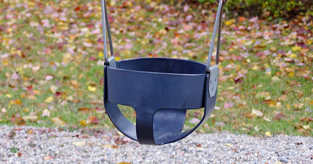 Empty baby swing in park in autumn