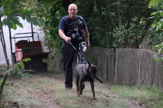 Un policier avec un chien renifleur arrive pour fouiller un jardin à Hanovre, dans le nord de l'Allemagne, le 29 juillet 2020. La police travaille sur le site dans le cadre de l'enquête sur l'affaire Madeleine 'Maddie' McCann.
