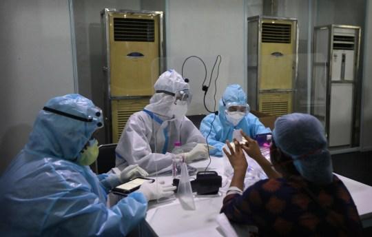 Une femme montre son numéro de file d'attente alors que des volontaires de la santé indiens l'enregistrent pour un camp d'étude test COVID-19 du raid non invasif Inde-Israël, dans un hôpital gouvernemental de New Delhi, en Inde, le vendredi 31 juillet 2020. Une équipe de scientifiques israéliens sont dans le pays pour effectuer les dernières étapes de test des technologies de pointe pour un diagnostic rapide en temps réel du coronavirus.