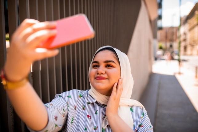 muslim girl wearing headscarf taking a selfie on her phone