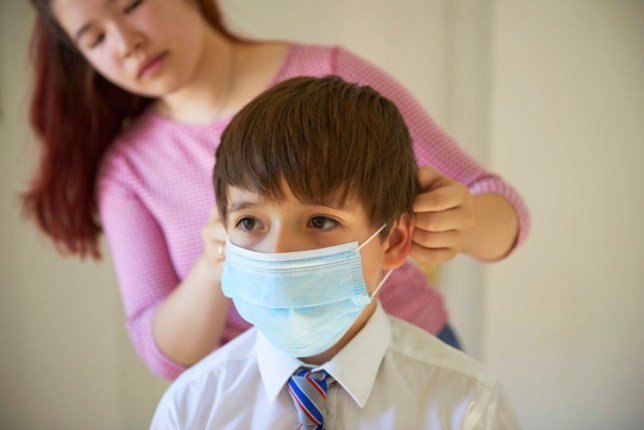 Mother applying facemask child going to school