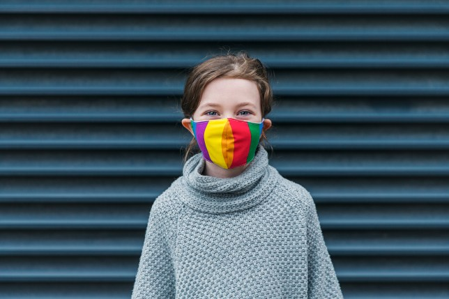 Young girl smiling behind her rainbow mask