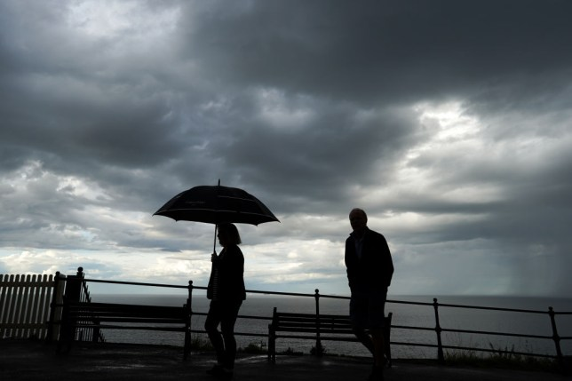 two silhouettes against a stormy sky