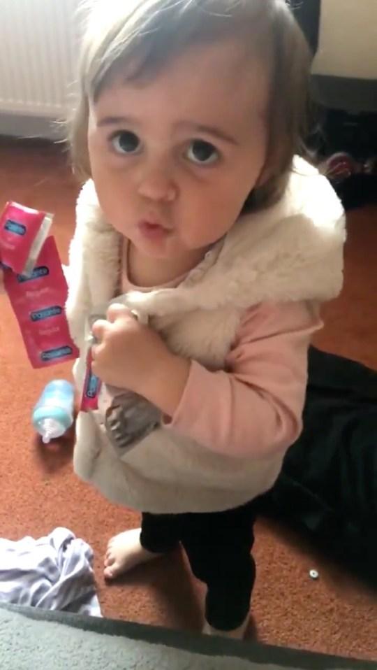 Toddler holding condoms