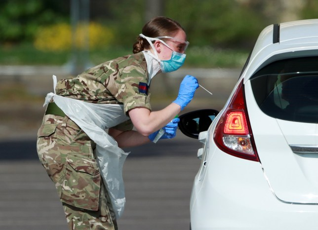 Military personnel are seen testing people at a coronavirus test centre in the car park of Chessington World of Adventures as the spread of the coronavirus disease (COVID-19) continues.