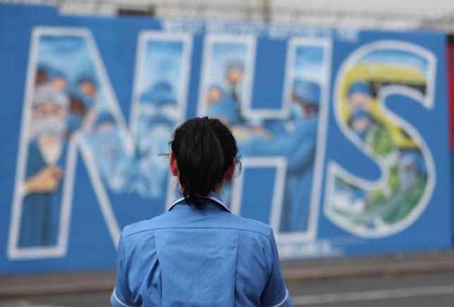 A nurse looks at a mural painted in recognition of the NHS on the Falls Road in Belfast, as the UK continues in lockdown to help curb the spread of the coronavirus. PA Photo. Picture date: Saturday April 18, 2020. See PA story HEALTH Coronavirus. Photo credit should read: Niall Carson/PA Wire