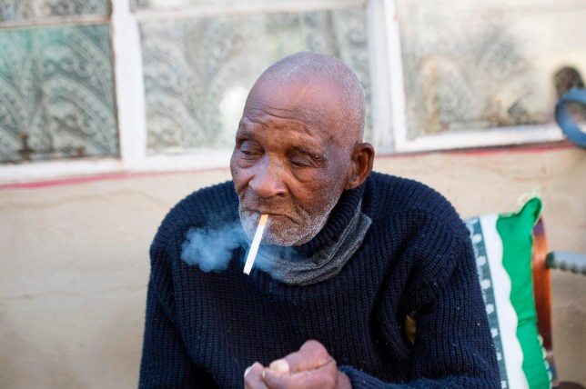 Fredie Blom enjoys a cigarette as he celebrates his 116th birthday at his home in Delft, near Cape Town, on May 8, 2020.