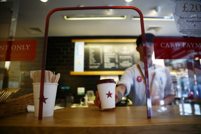 A coffee is passed to a customer at Pret