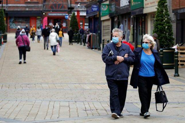 People wear protective face masks as they walk in Oldham, as the town faces local restrictions in an effort to avoid a local lockdown being forced upon the area amid the coronavirus disease (COVID-19) outbreak