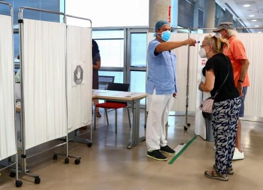 Une femme fait contrôler sa température par un agent de santé avant d'entrer dans un centre de soins primaires à Madrid, Espagne, le 24 juillet 2020. Photo prise le 24 juillet 2020. REUTERS / Sergio Perez