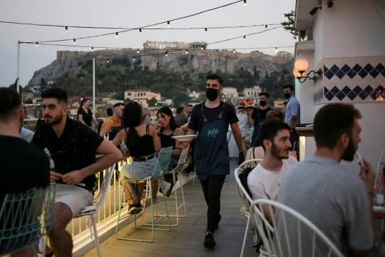 1 Αυγούστου 2020 Στην Αθήνα, Ελλάδα, εν μέσω της εξάπλωσης της νόσου της κορώνας (COVID-19), ένας υπάλληλος φορά μάσκα ασφαλείας ενώ εργαζόταν σε μπαρ.  Η εικόνα τραβήχτηκε την 1η Αυγούστου 2020.  REUTERS / Κώστας Μπαλτάς