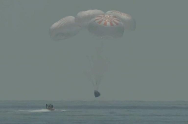 Dans cette capture d'image de NASA TV, la capsule SpaceX éclabousse dimanche 2 août 2020 dans le golfe du Mexique.  Les astronautes Doug Hurley et Bob Behnken ont passé un peu plus de deux mois sur la Station spatiale internationale.  Cela marquera le premier splashdown en 45 ans pour les astronautes de la NASA et la première fois qu'une entreprise privée a transporté des gens hors de leur orbite.  (NASA TV via AP) (NASA TV via AP)