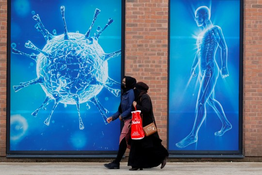 People walk past an illustration of a virus outside a regional science centre, as the city and surrounding areas face local restrictions in an effort to avoid a local lockdown being forced upon the region, amid the coronavirus disease (COVID-19) outbreak, in Oldham, Britain.