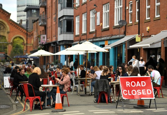 Diners sit at tables in a closed-off road in Manchester