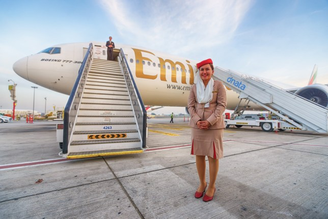 Air crew member stands outside an Emirates plane
