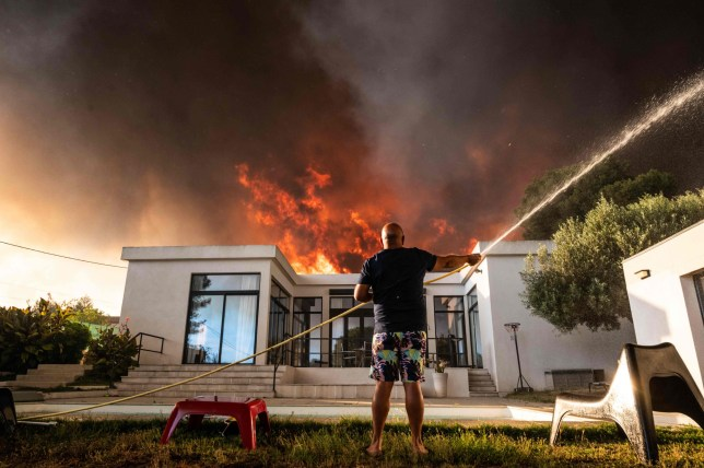 A man uses a garden hose to drench his house as a wild fire burns in the background, in La Couronne, near Marseille, on August 4, 2020. - Several fires were raging on August 4 evening near Marseille, with one particularly fuelled by strong winds, ravaging nearly 300 hectares of vegetation in a coastal area of Martigues, according to the authorities. (Photo by Xavier LEOTY / AFP) (Photo by XAVIER LEOTY/AFP via Getty Images)