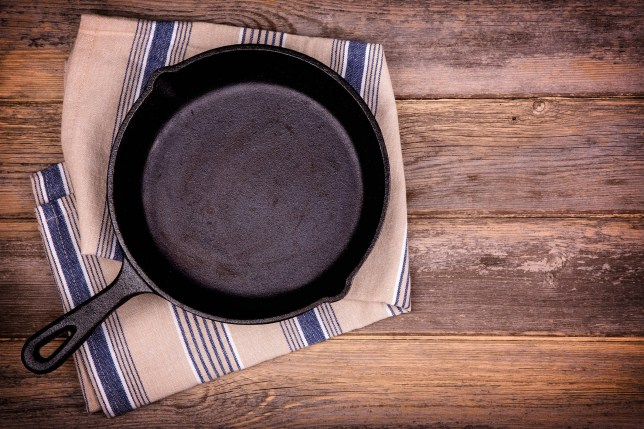 Empty cast iron skillet with tea towel, over old wood background. Retro style processing and space for your text.