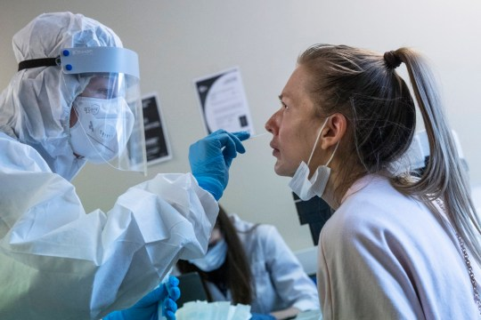 A medical worker, left, performs a COVID-19 test at a test center at Vnukovo airport outside Moscow, Russia, Friday, Aug. 7, 2020. Authorities in Russia say they are about to approve a COVID-19 vaccine, with mass vaccinations planned as early as October 2020, using shots that are yet to complete clinical trials. But scientists worldwide are sounding the alarm that the headlong rush could backfire and point to ethical issues that undermine confidence in the Russian studies. (AP Photo/Pavel Golovkin)