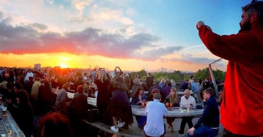 Les gens qui regardent le coucher du soleil au bar sur le toit Frank à Peckham