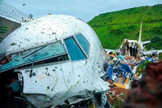 Des responsables inspectent l'épave d'un avion Air India Express à l'aéroport international de Calicut à Karipur, Kerala, le 8 août 2020. - Une pluie et des vents violents ont frappé un avion de passagers transportant 190 personnes de Dubaï qui s'est écrasé et s'est déchiré en deux dans un aéroport de le sud de l'Inde a tué au moins 18 personnes et blessé des dizaines d'autres, ont déclaré des responsables.  (Photo par Arunchandra BOSE / AFP) (Photo par ARUNCHANDRA BOSE / AFP via Getty Images)