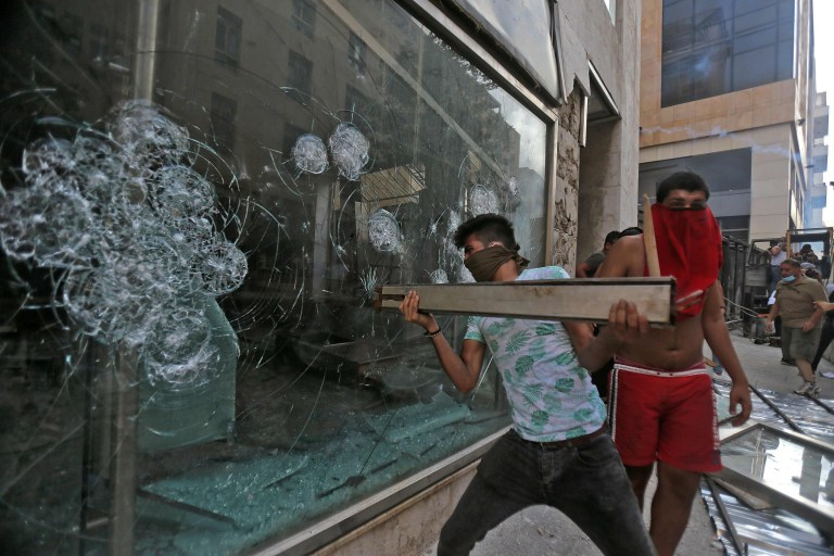 A Lebanese demonstrator breaks a shop window during clashes with security forces in downtown Beirut on August 8, 2020, following a demonstration against a political leadership they blame for a monster explosion that killed more than 150 people and disfigured the capital Beirut. (Photo by STR / AFP) (Photo by STR/AFP via Getty Images)