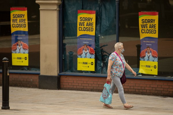 A woman wearing a protective face mask walks past a betting shop with posters in its windows informing customers of its closure, in the city centre of Preston, north west England on August 8, 2020, as local lockdown restrictions are reimposed due to a spike in cases of the novel coronavirus in the city. - Preston, in the north west of England, on Friday became the latest UK town to face a local lockdown due to a reported rise in coronavirus infection rates. Under the restrictions, which come into force at midnight, people from separate households will be banned from meeting each other at home. (Photo by OLI SCARFF / AFP) (Photo by OLI SCARFF/AFP via Getty Images)