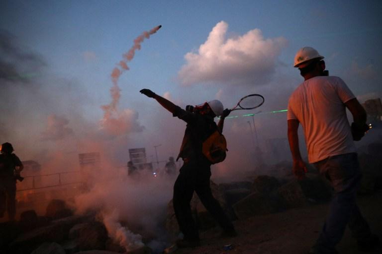 Un manifestant utilise une raquette de tennis pour frapper une cartouche de gaz lacrymogène lors d'une manifestation après l'explosion de mardi, à Beyrouth, au Liban, le 8 août 2020. REUTERS / Hannah McKay