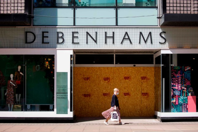 (FILES) In this file photo taken on May 29, 2020 A woman walks past closed Debenhams department store on Oxford Street in central London's main high street retail shopping area on May 29, 2020 ahead of some shops reopening from their coronavirus shutdown from next week. - UK department store chain Debenhams has axed 2,500 jobs, a spokesman said on August 11, 2020, as the coronavirus pandemic piles further pressure onto the long-suffering group. (Photo by Tolga AKMEN / AFP) (Photo by TOLGA AKMEN/AFP via Getty Images)