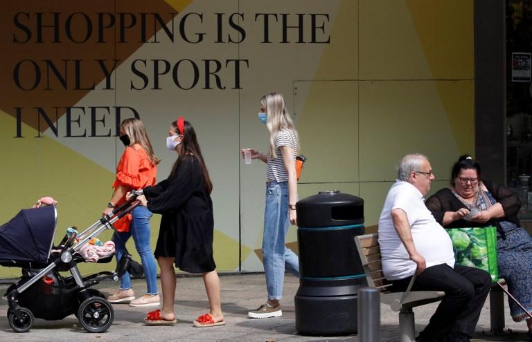 People walk past a closed retail unit following the outbreak of the coronavirus disease (COVID-19) in Warrington, Britain.