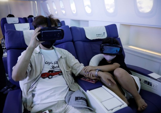A girl holds her father's hand as she uses a virtual reality (VR) device at a check-in desk at First Airlines, that provides VR flight experiences, including 360-degree tours of cities and meals, amid the COVID-19 pandemic in Tokyo, Japan