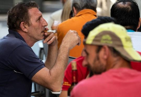 Un homme fume une cigarette sur la terrasse d'un bar à Valence le 13 août 2020. - Une interdiction de fumer dans les rues et les terrasses des restaurants lorsque la distanciation sociale ne peut être garantie est entrée en vigueur aujourd'hui dans la région nord-ouest de l'Espagne de la Galice, avec d'autres zones similaires restrictions pour freiner la propagation du coronavirus.  (Photo par JOSE JORDAN / AFP) (Photo par JOSE JORDAN / AFP via Getty Images)