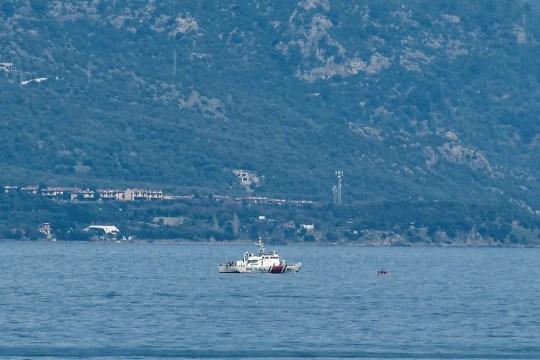 Un bateau des garde-côtes turcs procède à la vérification d'un bateau pneumatique en mer entre l'île de Lesbos et la côte turque dans le cadre d'opérations visant à empêcher les bateaux de réfugiés d'atteindre la côte grecque le 6 mars 2020 (photo de LOUISA GOULIAMAKI / AFP) (Photo par LOUISA GOULIAMAKI / AFP via Getty Images)