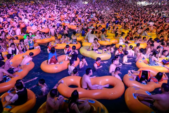 This photo taken on August 15, 2020 shows people watching a performance as they cool off in a swimming pool in Wuhan in China's central Hubei province. (Photo by STR / AFP) / China OUT (Photo by STR/AFP via Getty Images)