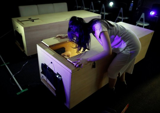 An actor dressed as zombie performs during a coffin horror show, performed by Kowagarasetai (Scare Squad), for people to lie inside a mock of coffin with a plastic shield in order to maintain social distancing amid the spread of the coronavirus disease (COVID-19), in Tokyo, Japan August 5, 2020. Picture taken August 5, 2020. REUTERS/Issei Kato