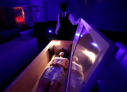 A participant lies inside a mock of coffin with plastic shields to maintain social distancing amid the spread of the coronavirus disease (COVID-19), during a coffin horror show, performed by Kowagarasetai (Scare Squad), in Tokyo, Japan August 22, 2020. REUTERS/Issei Kato