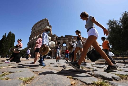 Les touristes, certains portant un masque facial, marchent devant le monument du Colisée