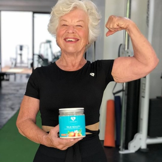 Joan holding up a jar of True Beauty and showing off her arm muscles