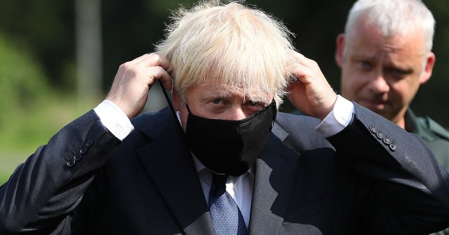 BELFAST, NORTHERN IRELAND - AUGUST 13: Prime Minister Boris Johnson puts on a face mask at the Northern Ireland Ambulance Service HQ during the Prime Minister's visit to Belfast on August 13, 2020 in Belfast, Northern Ireland. (Photo by Brian Lawless - WPA Pool/Getty Images)