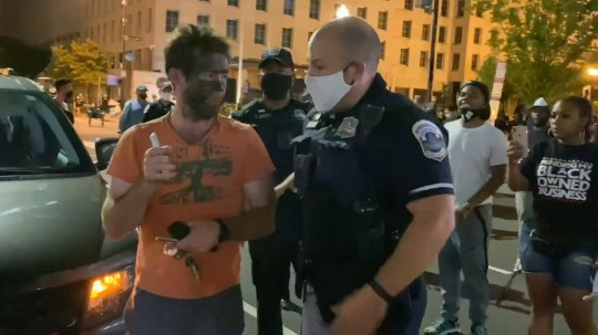 Washington D.C., USA, August 27,2020 (Video still)??????This is the shocking moment a protester in BLACK FACE was punched after sparking anger during rallies in Washington D.C. last night (August 27). The man was seen among crowds gathering closed to the White House while President Donald Trump formally accepted the GOP nomination. It was not clear which group the man in black face was supporting. However, there have been bizarre cases of white, BLM supporters, wearing black face in a misguided show of support for African Americans. Footage from cameraman Brendan Gutenschwager shows how he was ushered away by police before a furious Black Lives Matter protester punched him in the face and fled. Officers then gave chase and detained the alleged attacker by wrestling him to the ground to prevent him from leaving. The chaotic scenes unfolded as Trump gave an historic speech in the Rose Garden. Angry crowds chanted and marched through the streets of the city before moving towards the White House. They included Democrat activists and Black Lives Matter supporters hoping that Joe Biden wins at the U.S. elections in November. Music blasted while protesters marched and danced along to Hip-Hop music. Demonstrators were seen climbing on buses, honking with bullhorns and electric sirens blaring. They voiced anger over the death of George Floyd in Minneapolis, Minnesota, on May 25, the death of Breonna Taylor in Louisville, Kentucky, on March 13 and most recently the case of Jacob Blake, who was shot seven times in the back by a policeman in Kenosha, Wisconsin, on August 23.