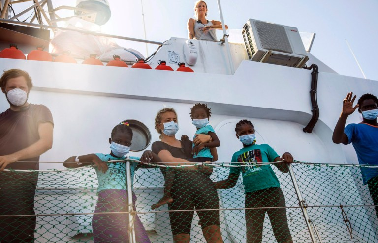 Crew members and rescued workers stand on the deck of the Louise Michel rescue vessel, a French patrol boat currently manned by activists and funded by the renowned artist Banksy in the Central Mediterranean sea, at 50 miles south from Lampedusa, , Friday, Aug. 28, 2020.