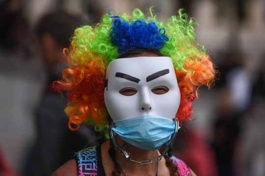 A woman wears two masks at an anti-mask rally.
