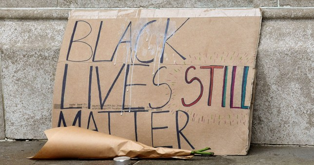 A placard is pictured near the sculpture of a Black Lives Matter protester standing on the empty plinth previously occupied by the statue of slave trader Edward Colston, in Bristol, Britain, July 15, 2020. REUTERS/Rebecca Naden