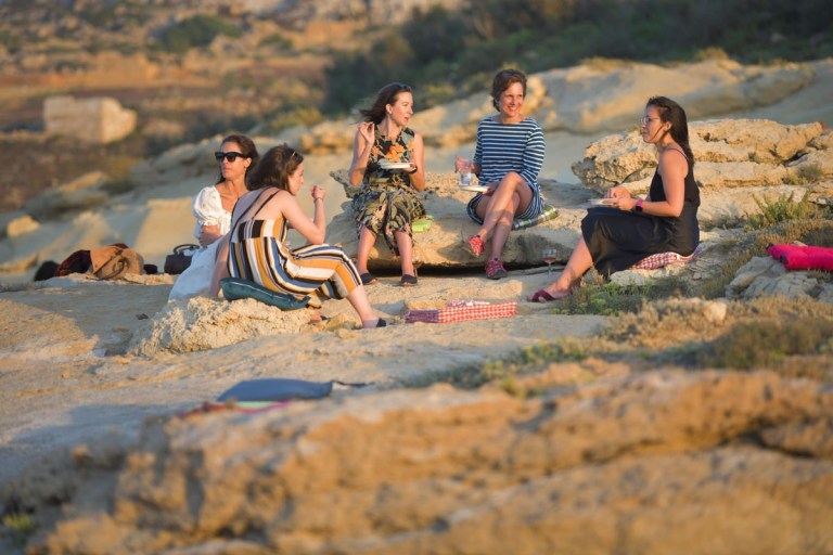 group of women eating a picnic on the beach in gozo