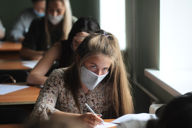 A young woman wearing a face mask in a classroom.